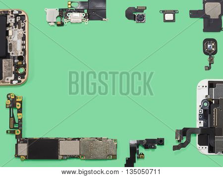 Flat lay (top view) of smart phone components isolate on green background with copy space