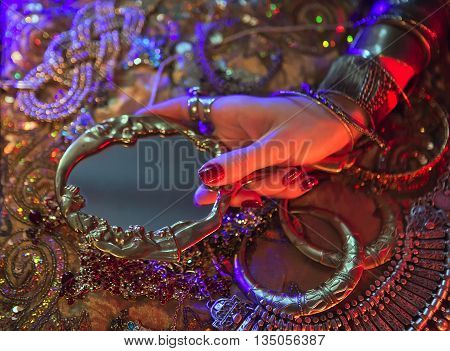 Golden Shiny Oriental Jewelry and Accessories: Female Hands with beautiful National Indian Jewellery Eastern Fairy Tale (Harem) Wedding Luxury Fashion and Beauty. Traditional Sari clothes Mirror. Color lenses