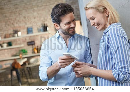 Happy young couple using mobilephone at home, looking at photos, laughing.