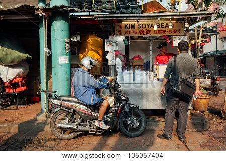 KUALA LUMPUR MALAYSIA - MARCH 17: People bying food from popular soya stall at Petaling Street in Chinatown Kuala Lumpur Malaysia on March 17 2016.