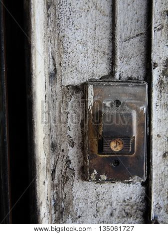 Old Door Bell On Dirty White Wall