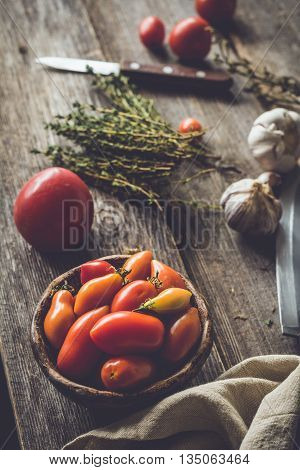 Heirloom tomatoes, banch of thyme springs, garlic and knife on rustic wooden table. Atmospheric rustic still life of tomatoes