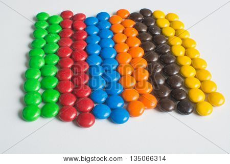 Pile of colorful chocolate bonbon candies sorted and organised into rows on white background