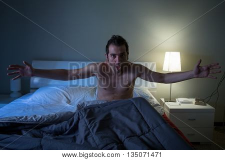 Man sleepless in his bed screaming after a terrible nightmare