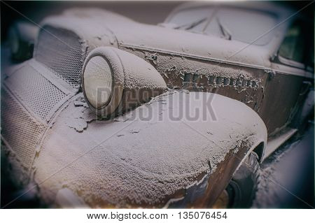 Old abandoned rusty car covered with snow