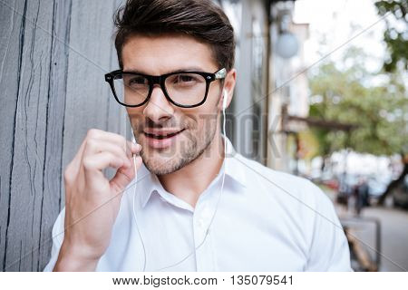Handsome young man in glasses walking outdoors and talking on the phone with handsfree