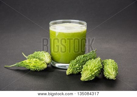 Herbal juice of green momodica in a glass with sliced vegetables, karela juice or bitter gourd juice