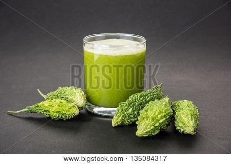 Herbal juice of green momodica in a glass with sliced vegetables, karela juice or bitter gourd juice