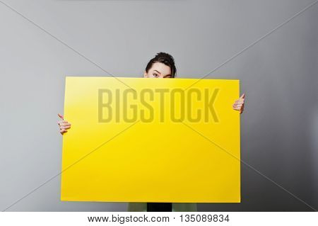 Banner Sign Woman Peeking Over Edge Of Blank Empty Yellow Paper Billboard With Copy Space For Text.