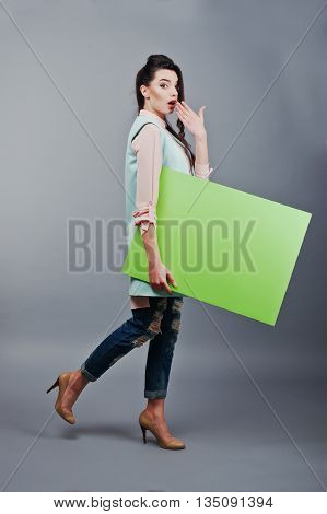 Young Girl With Surprised Face Hold Green Blank Paper. Young Smiling Woman Show Blank Card. Girl Wit