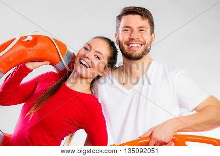 Accident prevention and water rescue. Young man and woman lifeguard couple on duty holding ring buoy float lifesaver equipment on gray