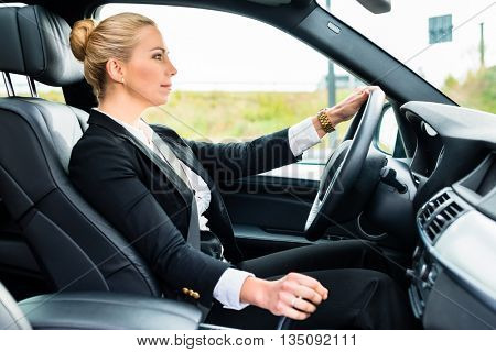 Woman driving in her car in business attire, travelling