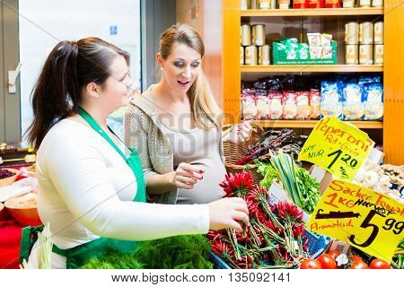 Customer and sales clerk in delicatessen store