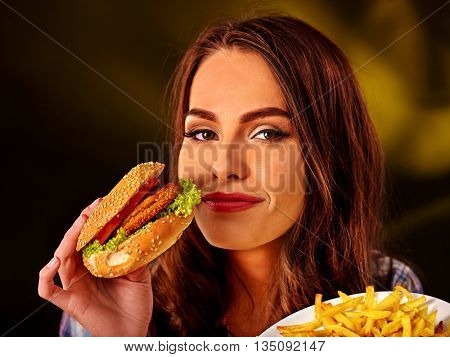 Happy girl holding fastfood hamburger and fried potatoes . Fastfood concept fastfood hamburger and fried potatoes on green.