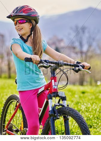 Bicycling child. Girl rides bicycle. Happy little girl in bycycling on mountains background. Cycling is good for child health. Bicyclist look away.
