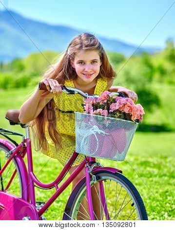 Bicycle girl. Teenager girl wearing yellow polka dots dress keeps bicycle with flowers basket. Lot of green tree and blu sky in park. Romantic bicycle style.
