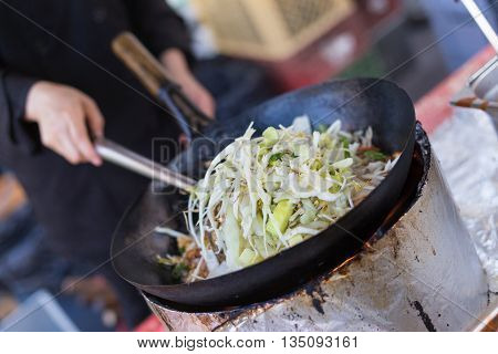 Chef cooking traditional Thai noodles, Pad Thai, on street stall on international street food festival of Odprta kuhna, Open kitchen event, in Ljubljana, Slovenia.