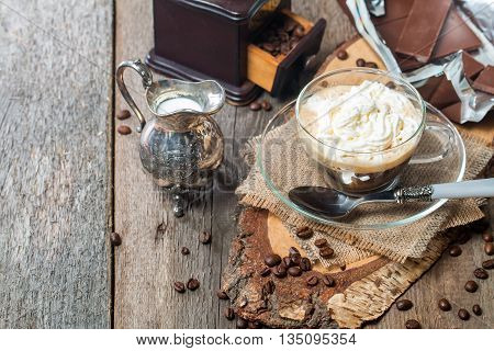 Glass cup of coffee with cream, chocolate and creamer on old wooden table
