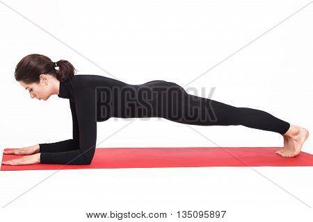 Beautiful athletic girl in black suit doing yoga. Kumbhasana asana plank pose on elbows. Isolated on white background.