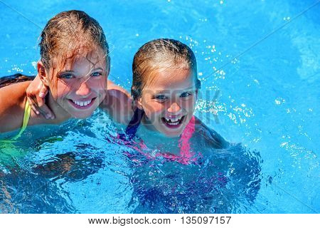 Two different ages children hugging and looking up swim in swimming pool. Summer swimming holiday. Outdoor swimming pool. Children activities lifestyle.