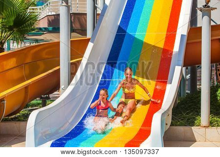 Two different ages children at aquapark slide down water slide. Summer aquapark holiday. Outdoor water slide.