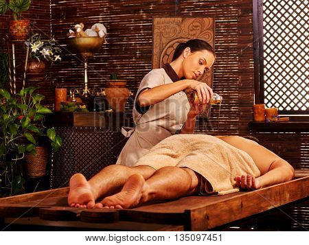 Man lays her head to window having oil Ayurveda spa massage. Massage girl pouring massage oil on man back.