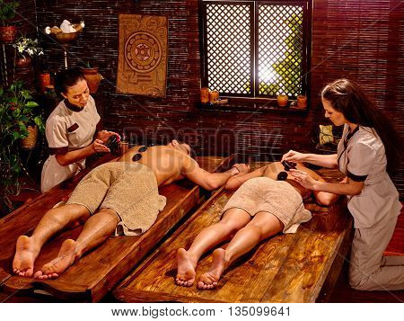 Couple lays her head to window having stone massage. Ayurveda lastone spa treatment.