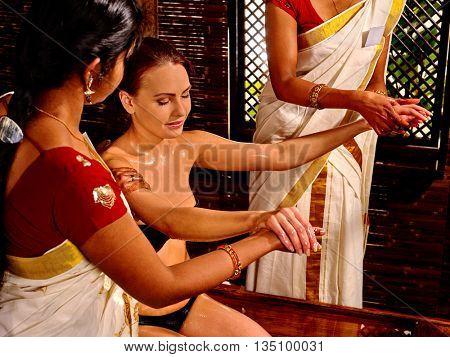 Seminude white woman having pouring oil massage in spa Indian massage salon.