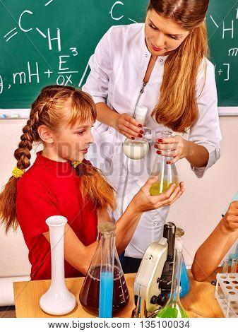 Child girl and chemistry teacher holding chemistry flask in chemistry class on chemistry lesson.