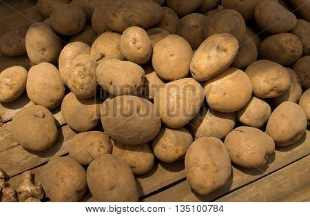 Potatoes on the wooden table, raw potato vegetable food in market