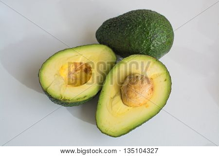 Fress hass green avocado sliced in half on light background