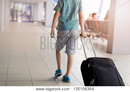 Boy Carrying His Luggage At Airport