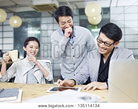 a team of young asian entrepreneurs having fun while working in office.