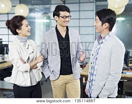 three young asian business people standing in office chatting.