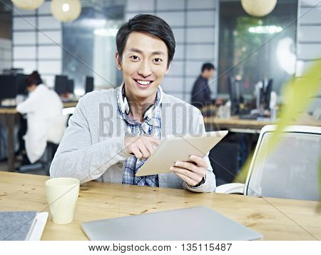 young asian business man sitting at desk in office holding tablet computer looking at camera smiling.