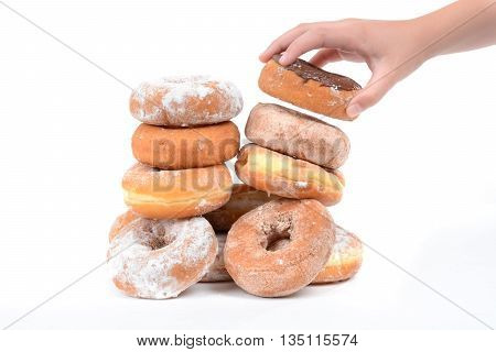 little hand grabbing a donut from a pile isolated on a white background