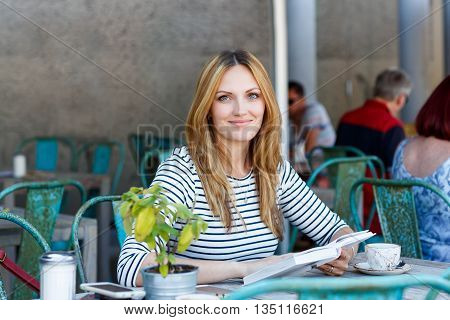 Young beautiful woman drinking coffee and reading book in an outdoor cafe in Paris, France