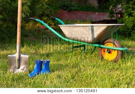 Blue rubber boots on a background of green lawn. Trolley and shovel for the garden care. Bright inventory gardener.