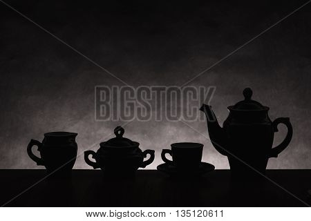 Dark silhouettes of ware for coffee on a gradient non-uniform background