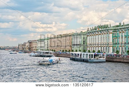 SAINT - PETERSBURG, RUSSIA - JUNE 20, 2016: Hydrofoil moors to the pier on The Neva River. On the right side is  The State Hermitage Building (Winter Palace)