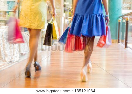 Two women walking with shopping bags at the shopping mall, blur