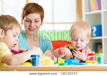 woman teaching children handcraft at kindergarten or playschool