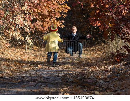 Funny Baby Girl Running towards Open Arms of Her Father along Alley in Autumnal Forest
