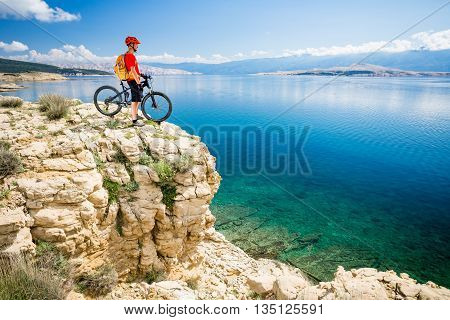 Mountain biker looking at view and traveling on bike in summer sea landscape. Man rider cycling MTB on country road or single track. Fitness motivation inspiration in beautiful inspirational view Croatia.