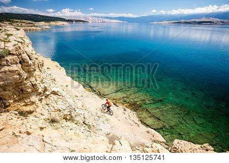 Mountain biker riding on bike in summer inspirational mountains and sea landscape view. Man cycling MTB on enduro dirt and rocky trail track. Fitness motivation beautiful inspirational view Croatia.