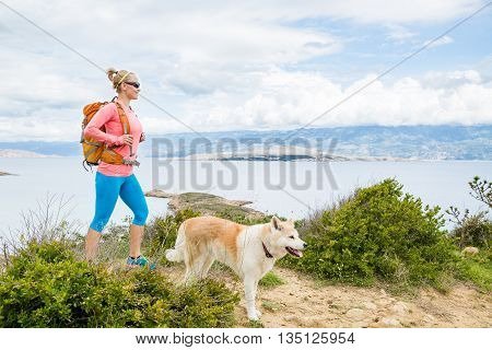 Woman hiking with akita inu dog on seaside trail. Recreation and healthy lifestyle outdoors in summer mountains and sea nature. Beautiful inspirational landscape. Trekking and activity concept.