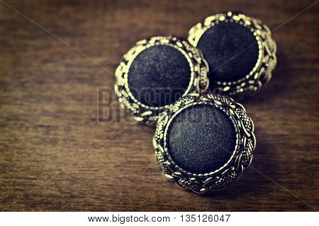 Round metal buttons in vintage style on a wooden background. Selective focus.
