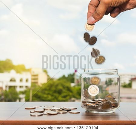 Close up glass bottle with hand stacking silver coins falling on wooden table