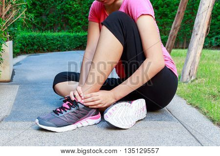 Asian sporty woman ankle sprain while jogging or running concept
