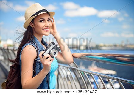 Relaxed young girl is making travel. She is standing near a border and enjoying river scenery. Tourist is looking at camera and smiling